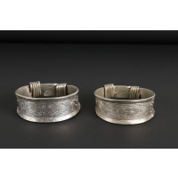 Pair of silver bracelets engraved with floral motifs and spiral clasp