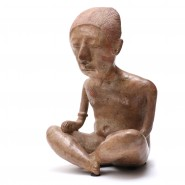 Superb figure sitting cross-legged, probably a shaman, decorated with a long braid in the back